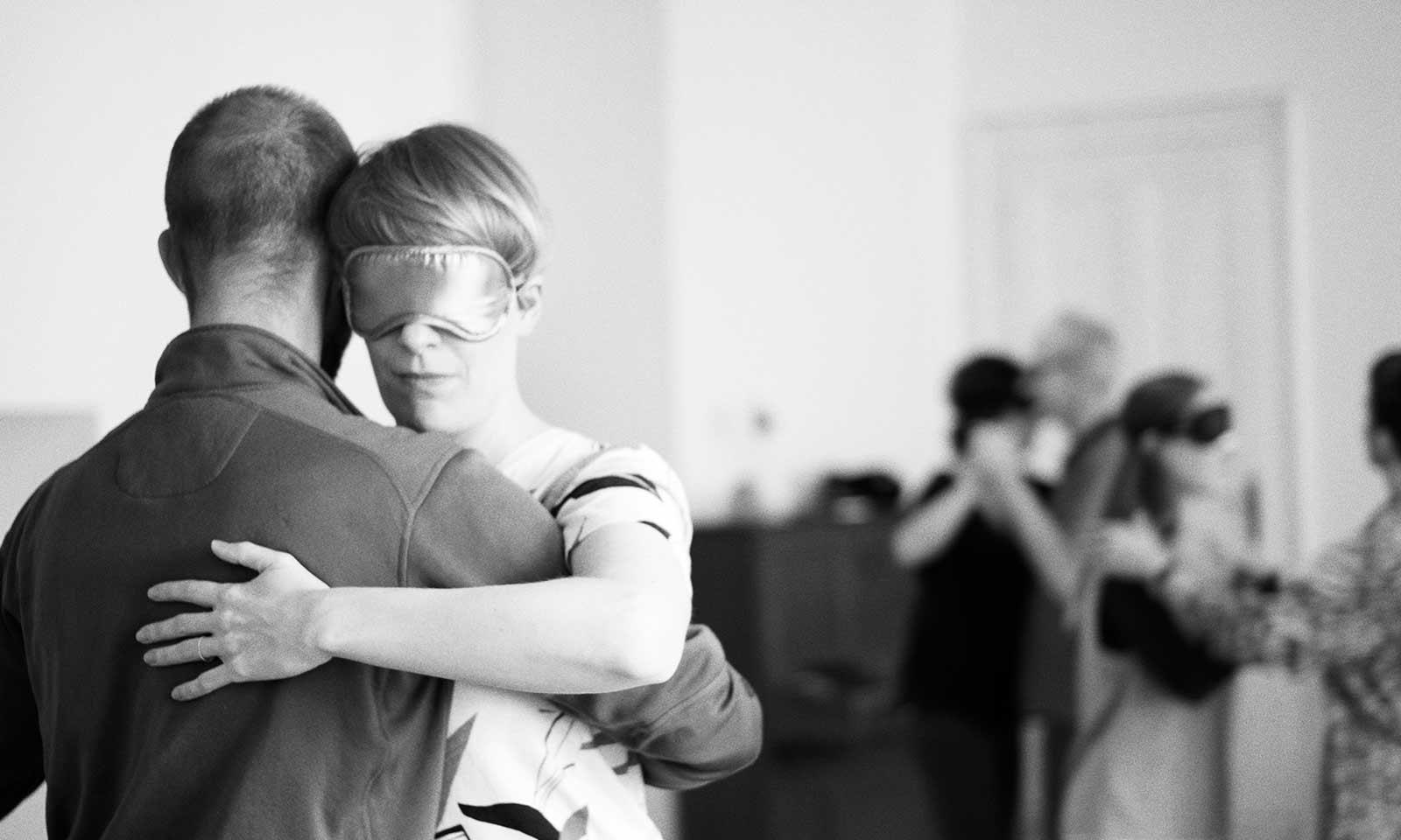 Tanzpaare mit Augenmasken, im Vordergrund ein Paar in enger Tanzhaltung und ebenfalls mit Augenmaske