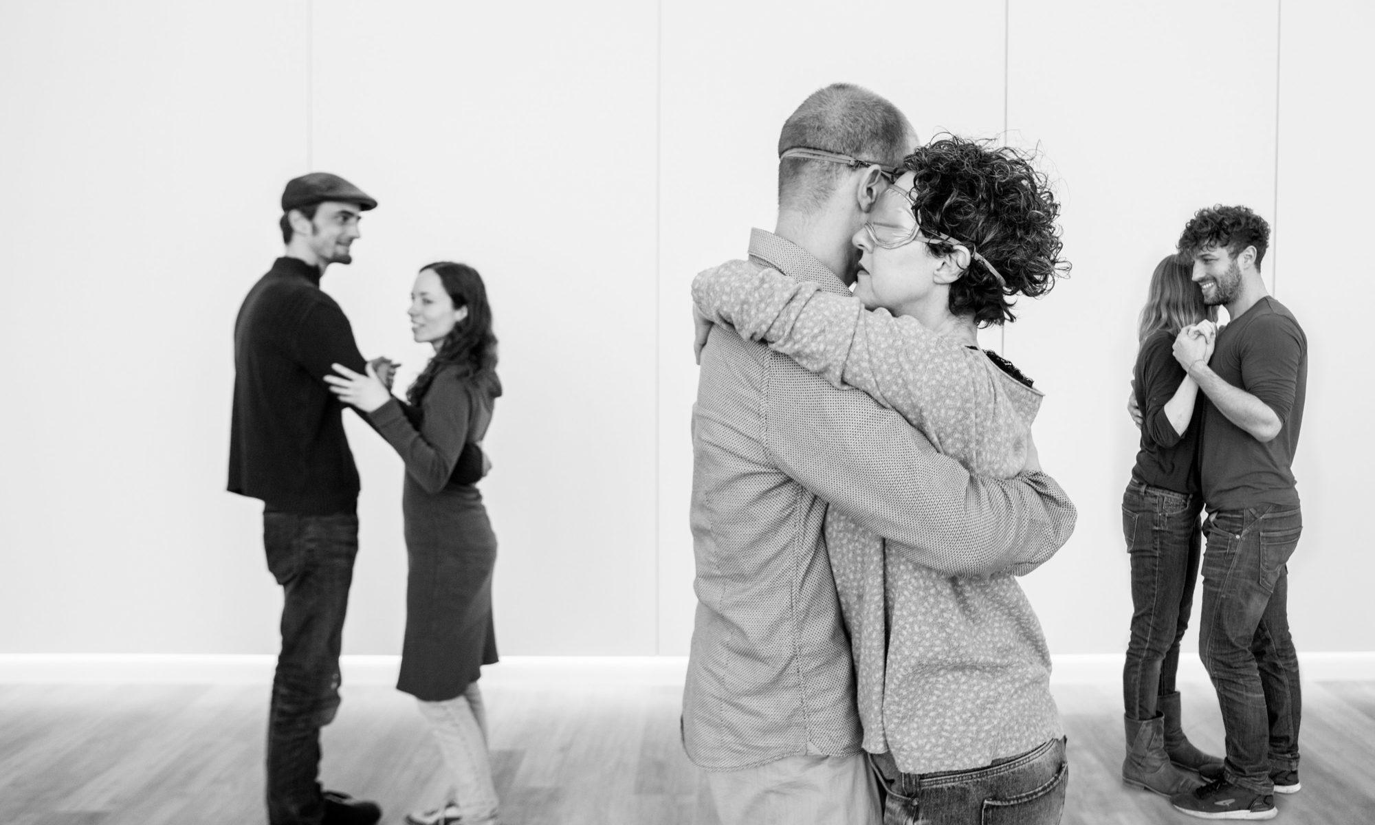 Schwarz-weiß Bild, drei tanzende Paare im Studio von Lillis Ballroom, im Vordergrund tanzt ein Paar mit verbundenen Augen