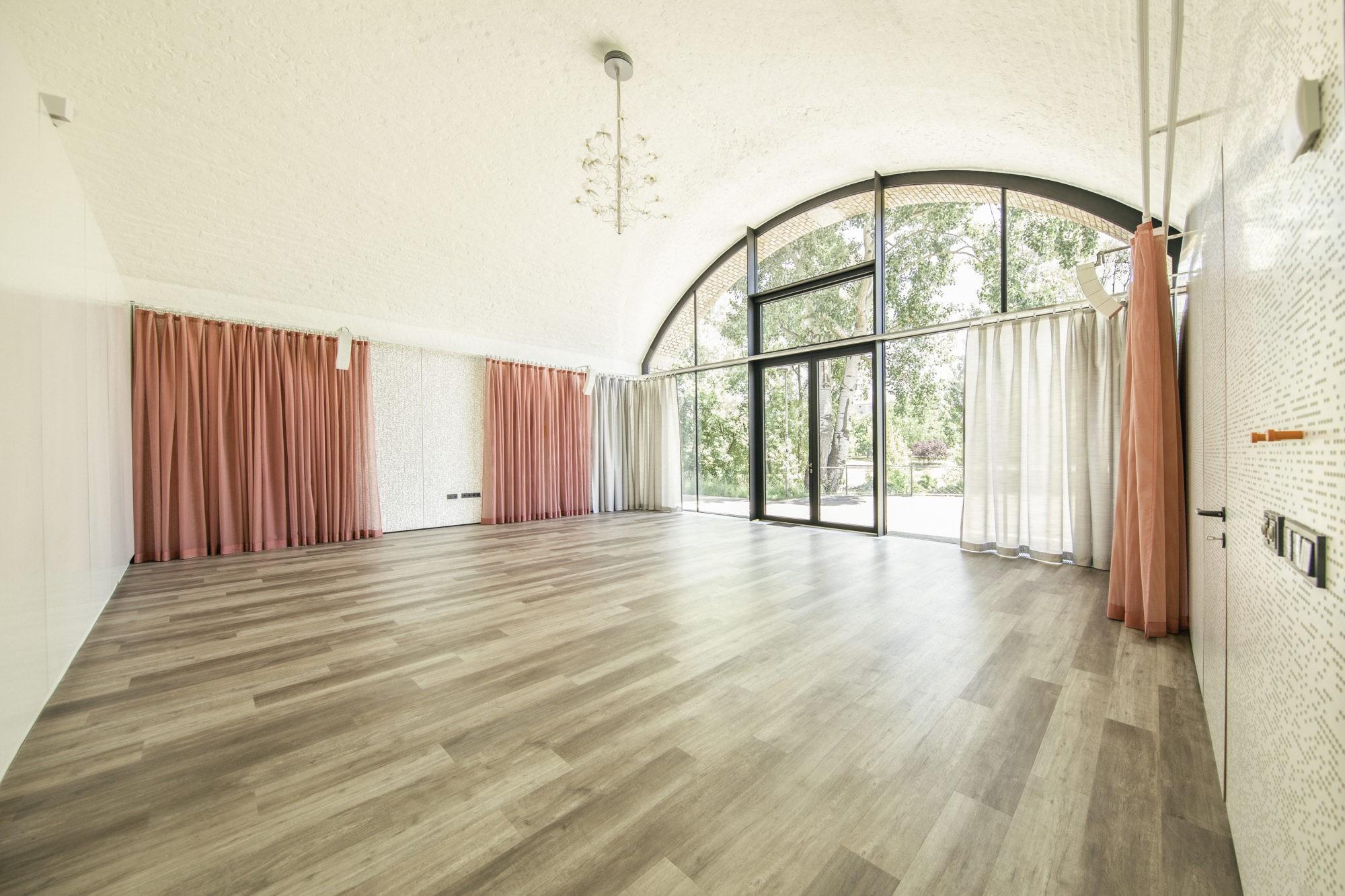Großer Tanzbogen Tanzstudio 1, schöner Tanzboden in Holzoptik, Vorhänge in grau und hellrot. Blick nach draußen zum grünen Donaukanal.