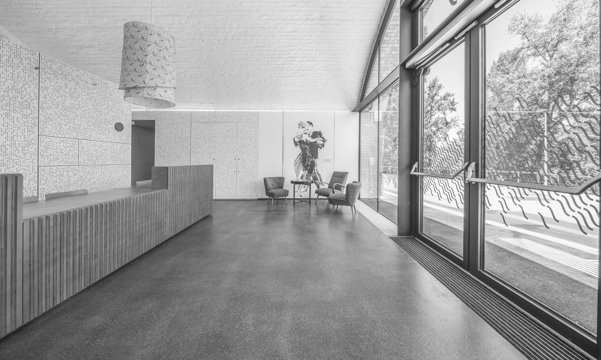 Eingang und Anmeldebereich mit Sitzgruppe und Wandbild eines Tango tanzenden Paares
