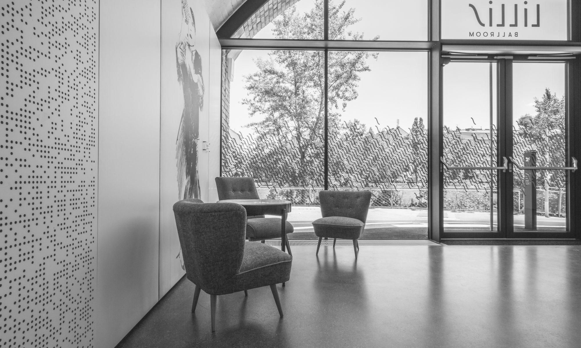 3 Sessel und ein Tisch stehen im Eingangsbereich vor der Fensterfront