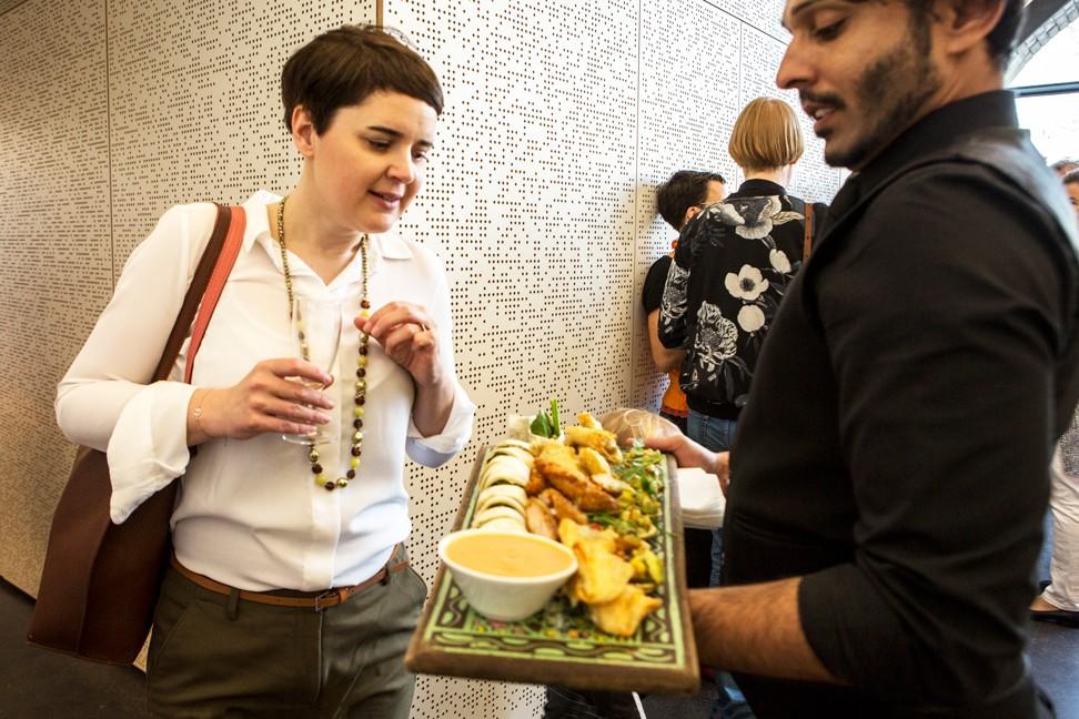 Ein Kellner hält ein Servierbrett mit Fingerfood. Eine Dame steht vor ihm und wählt etwas aus.