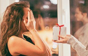 Frau hält sich die Augen zu und bekommt ein Päckchen überreicht