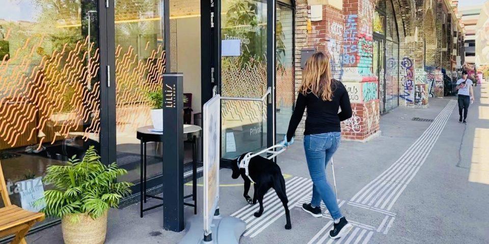 Unsere Mitarbeiterin Nadine geht mit ihrem Blindenhund Flora und Blindenstock über das Leitsystem in den Eingang zum den Tanzstudios von Lillis Ballroom