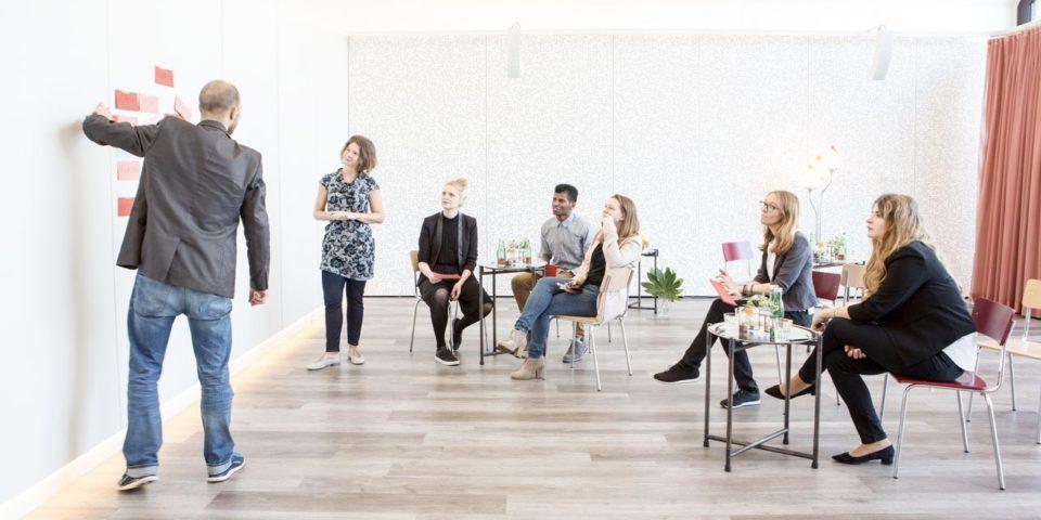 Ein Herr zeigt anhand von Kärtchen an der Wand etwas vor. An zwei kleinen Kaffeehaus Tischen sitzen 5 Menschen und hören interessiert zu. Eine Dame steht und hört zu.